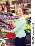 Купить «happy woman with shopping trollye buying flowers», фото № 20086851, снято 25 февраля 2015 г. (c) Syda Productions / Фотобанк Лори