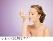 Купить «woman smelling perfume from wrist of her hand», фото № 20088711, снято 31 октября 2015 г. (c) Syda Productions / Фотобанк Лори
