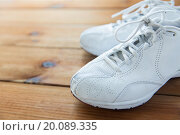 Купить «close up of sneakers on wooden floor», фото № 20089335, снято 15 октября 2015 г. (c) Syda Productions / Фотобанк Лори