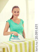 Купить «happy woman with iron and ironing board at home», фото № 20091631, снято 25 января 2015 г. (c) Syda Productions / Фотобанк Лори