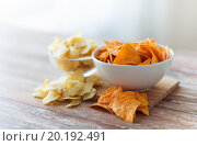Купить «close up of potato crisps and nachos in glass bowl», фото № 20192491, снято 22 мая 2015 г. (c) Syda Productions / Фотобанк Лори