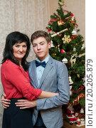 Купить «Взрослая мама с сыном стоят в обнимку возле новогодней ёлки», эксклюзивное фото № 20205879, снято 1 января 2016 г. (c) Игорь Низов / Фотобанк Лори