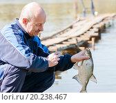 Купить «Рыбак снимает пойманного леща с крючка», эксклюзивное фото № 20238467, снято 7 мая 2015 г. (c) Игорь Низов / Фотобанк Лори
