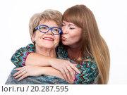 Купить «Взрослая дочь обнимает и целует пожилую маму, белый фон», фото № 20287595, снято 13 декабря 2015 г. (c) Кекяляйнен Андрей / Фотобанк Лори