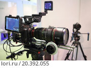 Купить «MOSCOW - MAR 12, 2014: Professional digital video camera on a tripod at the exhibition in Expo Center in Moscow, close-up», фото № 20392055, снято 12 марта 2014 г. (c) Losevsky Pavel / Фотобанк Лори