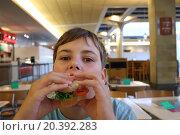 Купить «Little boy is eating sandwich at fast food cafe.», фото № 20392283, снято 5 сентября 2014 г. (c) Losevsky Pavel / Фотобанк Лори