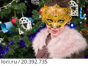 Купить «Close up view of young woman in gold masquerade mask is standing near christmas tree.», фото № 20392735, снято 18 декабря 2014 г. (c) Losevsky Pavel / Фотобанк Лори