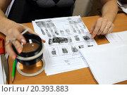 Купить «Woman is looking at fingerprint and taking magnifier.», фото № 20393883, снято 14 ноября 2014 г. (c) Losevsky Pavel / Фотобанк Лори