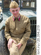 Купить «NELIDOVO, RUSSIA- JULY 12, 2014: Battlefield 2014: Soviet soldier sitting on the hood of a truck», фото № 20394219, снято 12 июля 2014 г. (c) Losevsky Pavel / Фотобанк Лори
