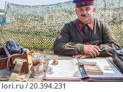 Купить «NELIDOVO, RUSSIA- JULY 12, 2014: Battlefield 2014: lieutenant of the Red Army at the desk», фото № 20394231, снято 12 июля 2014 г. (c) Losevsky Pavel / Фотобанк Лори