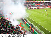 Купить «MOSCOW, RUSSIA - MAR 30, 2014: Fans launching smoke flare during a match at the stadium Locomotive», фото № 20396171, снято 30 марта 2014 г. (c) Losevsky Pavel / Фотобанк Лори