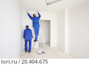 Купить «Two workers in blue clothes glue paint fiberglass on ladder in new apartment», фото № 20404675, снято 11 декабря 2013 г. (c) Losevsky Pavel / Фотобанк Лори