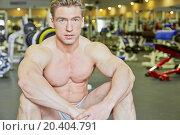 Купить «Bodybuilder sits on floor in gym hall taking rest», фото № 20404791, снято 4 апреля 2013 г. (c) Losevsky Pavel / Фотобанк Лори
