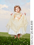 Купить «Little girl in beautiful beige gown and crown on head stands on grassy meadow, lifting up slightly hem of external skirt», фото № 20404899, снято 9 июня 2013 г. (c) Losevsky Pavel / Фотобанк Лори