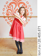 Купить «Smiling girl in red folk costume with performs near wall with pattern», фото № 20405871, снято 27 декабря 2013 г. (c) Losevsky Pavel / Фотобанк Лори