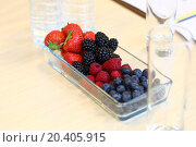 Купить «Strawberries, blackberries, raspberries, blueberries in a glass vase on the office desk», фото № 20405915, снято 10 октября 2013 г. (c) Losevsky Pavel / Фотобанк Лори