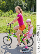Купить «Mother rides bicycle and her daughter in rollers sits on rear bike rack on sunny day in park», фото № 20406251, снято 13 июля 2013 г. (c) Losevsky Pavel / Фотобанк Лори