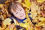 Closeup portrait of boy who lies on ground strewn with yellow fallen leaves in autumn park, фото № 20406319, снято 13 октября 2013 г. (c) Losevsky Pavel / Фотобанк Лори