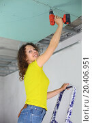 Купить «Woman with an electric screwdriver to fasten drywall on ceiling», фото № 20406951, снято 20 июля 2013 г. (c) Losevsky Pavel / Фотобанк Лори