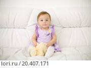 Купить «Little baby in dress with toy sits on white sofa at home. Shallow depth of field.», фото № 20407171, снято 23 октября 2013 г. (c) Losevsky Pavel / Фотобанк Лори