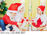 Купить «Three children in santa caps sit on fur rug and look at decorative lighting with fishes inside», фото № 20408487, снято 24 ноября 2013 г. (c) Losevsky Pavel / Фотобанк Лори