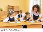 Купить «Two girls and boy write at school desks in classroom and teacher helps at school.», фото № 20408915, снято 17 августа 2013 г. (c) Losevsky Pavel / Фотобанк Лори