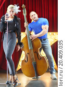 Купить «Beautiful girl with microphone and man with big muscles with contrabass on stage», фото № 20409035, снято 19 апреля 2014 г. (c) Losevsky Pavel / Фотобанк Лори