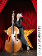 Купить «Portrait of a beautiful girl contrabass on stage at music hall», фото № 20409119, снято 19 апреля 2014 г. (c) Losevsky Pavel / Фотобанк Лори