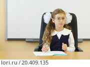 Купить «Girl in glasses and vest sits at teacher table with exercise book in classroom at school.», фото № 20409135, снято 17 августа 2013 г. (c) Losevsky Pavel / Фотобанк Лори