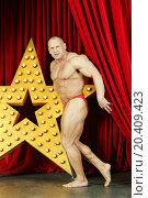 Bodybuilder demonstrates his physique on stage with big lights star. Стоковое фото, фотограф Losevsky Pavel / Фотобанк Лори
