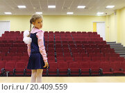 Купить «Sad girl with braids and bows stands on stage front of empty auditorium and looks at camera», фото № 20409559, снято 17 августа 2013 г. (c) Losevsky Pavel / Фотобанк Лори