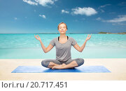 Купить «woman making yoga meditation in lotus pose on mat», фото № 20717451, снято 13 ноября 2015 г. (c) Syda Productions / Фотобанк Лори