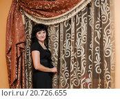 Купить «Привлекательная тёмноволосая женщина среднего возраста стоит возле красивой шторы», эксклюзивное фото № 20726655, снято 12 июля 2015 г. (c) Игорь Низов / Фотобанк Лори