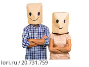 Couple with arms crossed wearing smiley paper bags. Стоковое фото, агентство Wavebreak Media / Фотобанк Лори