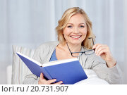 Купить «smiling woman reading book and sitting on couch», фото № 20731907, снято 27 ноября 2015 г. (c) Syda Productions / Фотобанк Лори