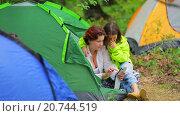 Купить «Две девушки смотрят фотографии на смартфоне, сидя в палатке в лагере в лесу», видеоролик № 20744519, снято 16 августа 2015 г. (c) Tatiana Kravchenko / Фотобанк Лори