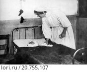 France: November 21, 1914 A French nurse tends to a gravely wounded Belgian soldier who had penned a letter to his wife about the baby shoes he had purchased... (2015 год). Редакционное фото, фотограф UNDERWOOD ARCHIVES / age Fotostock / Фотобанк Лори