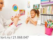 Купить «Симпатичная дошкольница выполняет пальчиковые упражнения, сидя за партой в классе», фото № 21068047, снято 12 декабря 2015 г. (c) Сергей Новиков / Фотобанк Лори