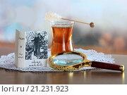 Миниатюрная книга с лупой и чашкой чая на деревянном столе (2016 год). Редакционное фото, фотограф Татьяна Белова / Фотобанк Лори