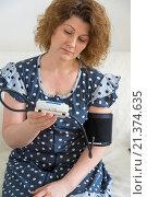 woman in a housecoat measures yourself blood pressure. Стоковое фото, фотограф Володина Ольга / Фотобанк Лори
