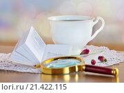 Миниатюрная книга с лупой и чашкой чая на  столе. Стоковое фото, фотограф Татьяна Белова / Фотобанк Лори
