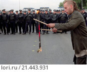 Young male protester juggling with fire whilst penned in by police during a demonstration in East London about the arms trade fair at the Excel Centre. Стоковое фото, фотограф Photofusion/UIG / age Fotostock / Фотобанк Лори