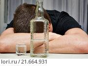 Парень спит за столом с бутылкой и рюмкой водки. Стоковое фото, фотограф Никита Ковалёв / Фотобанк Лори
