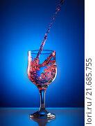 Льющаяся вода в винный бокал на синем фоне. Стоковое фото, фотограф Alex Ryabis / Фотобанк Лори