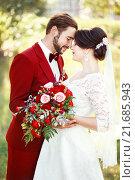 Купить «Невеста в белом платье и жених в темно-красном костюме стоят обнявшись», фото № 21685943, снято 30 августа 2015 г. (c) Евгений Майнагашев / Фотобанк Лори
