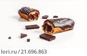 Шоколадные эклеры с кусочками шоколада на белом столе. Стоковое фото, фотограф Riasna Yuliia / Фотобанк Лори