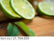 Купить «lime slices on wooden table», фото № 21704059, снято 21 декабря 2015 г. (c) Syda Productions / Фотобанк Лори
