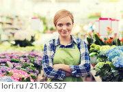 Купить «happy woman with flowers in greenhouse», фото № 21706527, снято 25 февраля 2015 г. (c) Syda Productions / Фотобанк Лори