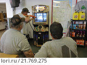 Three truckers playing a hunting video game at a petrol station, McLean, United States of America (2007 год). Редакционное фото, агентство Caro Photoagency / Фотобанк Лори