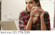 Купить «Smiling woman using laptop while drinking coffee», видеоролик № 21776539, снято 18 октября 2019 г. (c) Wavebreak Media / Фотобанк Лори